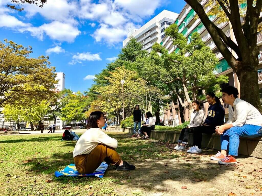 木の下で話し合う生徒